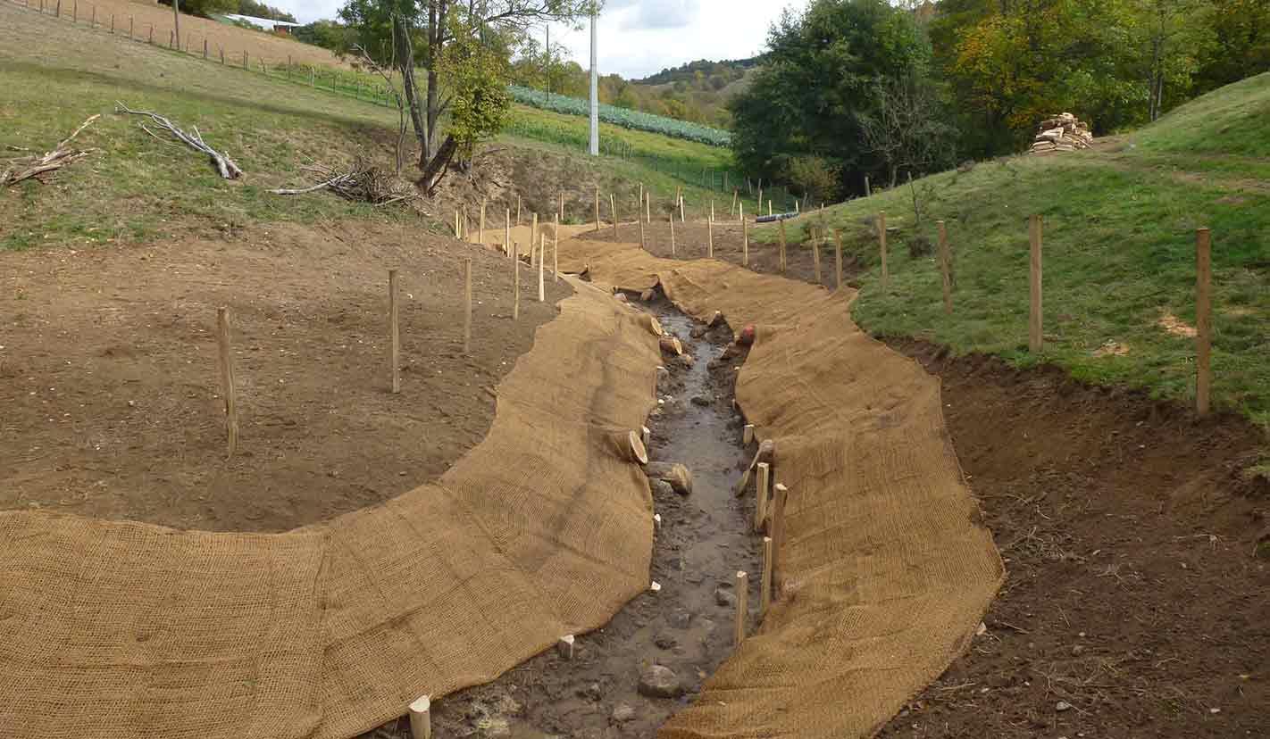La pose d'un géotextile en fibre de coco permet de stabiliser les berges le temps que la végétation grandisse et prenne le relais.